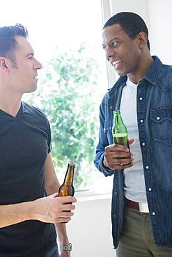 Men drinking beer near window