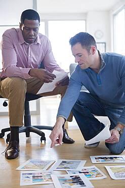 Businessmen examining paperwork on office floor
