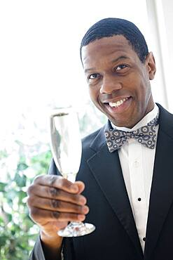 Smiling groom toasting with champagne