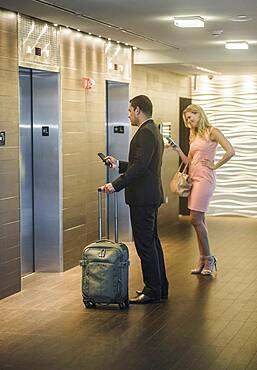 Business people using cell phones and waiting for elevator