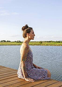 Caucasian woman sitting on wooden dock over lake