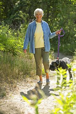 Older Caucasian woman walking dog on dirt path