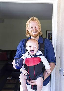 Caucasian father wearing son in harness in doorway
