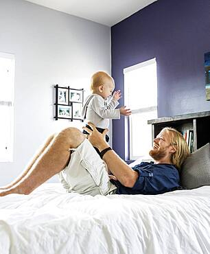 Caucasian father and son playing on bed