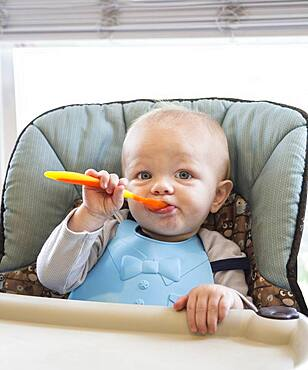 Caucasian baby boy eating in high chair