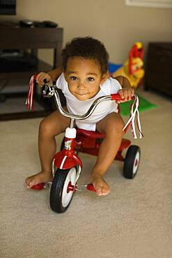Mixed race boy riding tricycle in living room