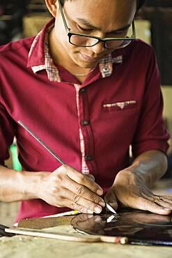 Asian artisan carving traditional design in workshop