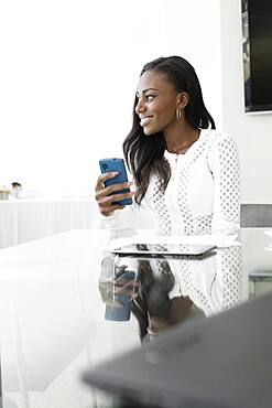 Businesswoman using cell phone in conference room