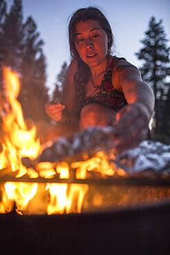 Caucasian woman cooking food over campfire