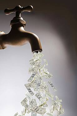 Dollar bills pouring out of faucet