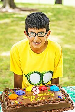 Hispanic boy smiling with birthday cake at party