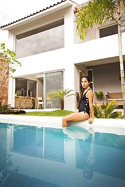 Hispanic woman sitting in swimming pool