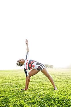Black woman practicing yoga in field