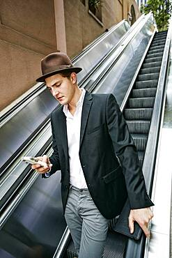 Caucasian businessman using cell phone on escalator