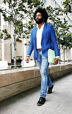 Mixed race businessman walking outdoors