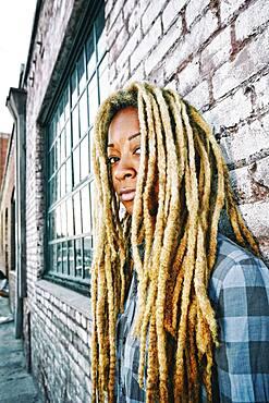 Black woman with dreadlocks at brick wall