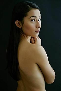 Nude Hispanic woman looking over shoulder