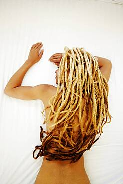 Black woman with dreadlocks laying on bed