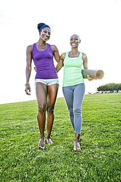 Women carrying yoga mat in park