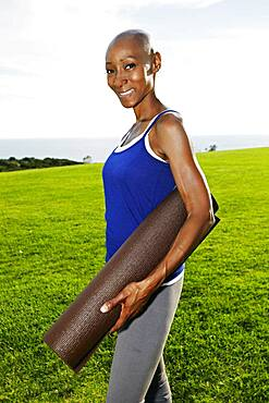 African American woman carrying yoga mat in park