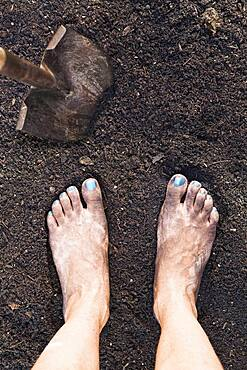 Mixed race woman barefoot in dirt