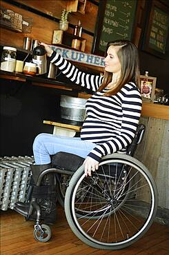 Paraplegic woman in wheelchair pouring coffee in cafe
