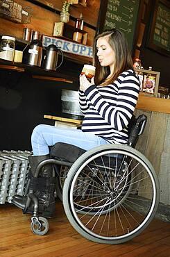 Paraplegic woman in wheelchair drinking coffee