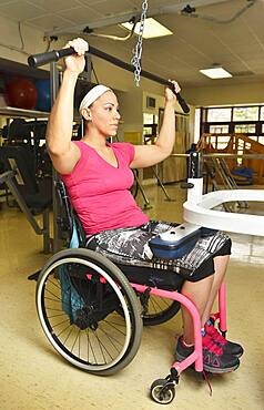 Paraplegic woman in wheelchair working out in physical therapy