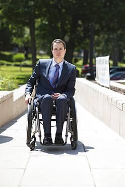 Paraplegic businessman in wheelchair on walkway