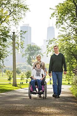 Parents pushing paraplegic daughter in wheelchair