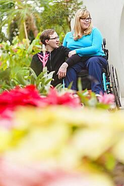 Man and paraplegic girlfriend exploring garden
