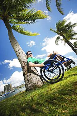 Disabled man playing in wheelchair on beach