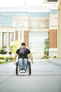 Disabled student rolling in wheelchair on college campus