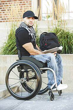 Disabled student in wheelchair reading book