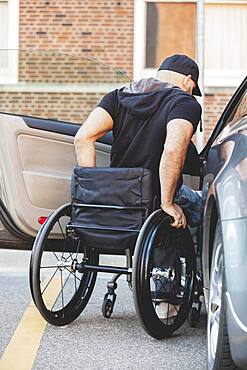 Disabled man in wheelchair climbing into car