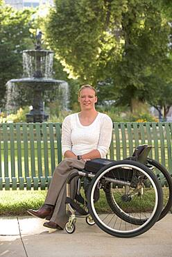 Disabled woman with wheelchair sitting on bench