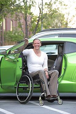 Disabled woman in wheelchair climbing into car