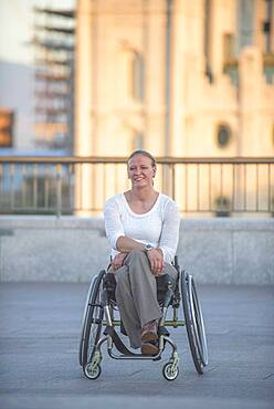 Disabled woman sitting in wheelchair on urban rooftop