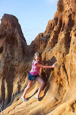 Caucasian girl climbing rock formations