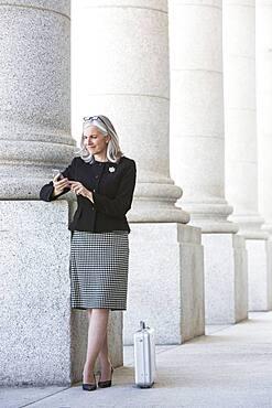 Caucasian businesswoman using cell phone under columns