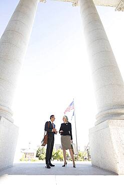 Business people talking under columns