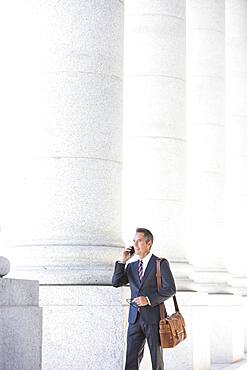 Mixed race businessman talking on cell phone under columns
