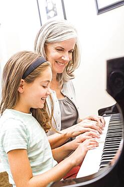 Caucasian woman giving student piano lessons