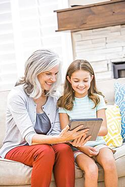 Caucasian grandmother and granddaughter using digital tablet on sofa
