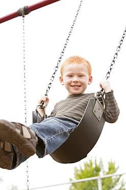 Caucasian boy sitting on playground swing