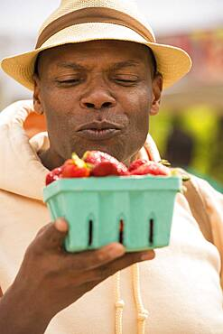 African American man examining basket of strawberries