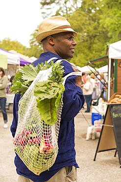 African American man carrying bag of produce at market
