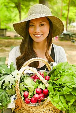 Asian woman carrying basket of produce