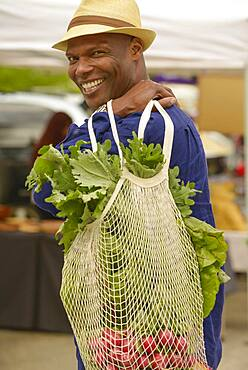 African American man carrying bag of vegetables