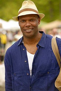 African American man wearing hat and tote bag